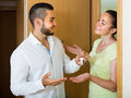 Couple with keys at the door young men giving to smiling women from a new apartment focus on man Royalty Free Stock Photography