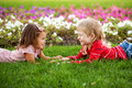 Couple of kids looking eye to eye love concept little boy and girl lying on the grass holding hands and Stock Photo