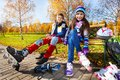Couple kids skating and years old of school boy an girl putting on roller blades in warm autumn clothes in the park shoot from low Stock Photos