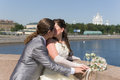 The couple kissing on a bridge on wedding day Stock Images