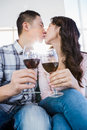 Couple kissing and holding wineglasses while relaxing at home Stock Image