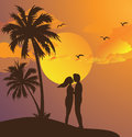 Couple kissing silhouette sunset on beach romantic moment yellow sky palm tree Royalty Free Stock Photo