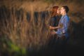 Couple kissing standing outdoos among bushes young Stock Photos