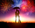 Couple kissing under umbrella with firework in the sky Stock Image
