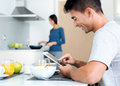 Couple in the kitchen preparing breakfast and browsing internet Royalty Free Stock Photo