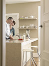 Couple in kitchen seen through open door happy standing at counter Royalty Free Stock Photography