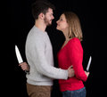 Couple with knives young smiling while holding behind their backs ready to stab Royalty Free Stock Photo