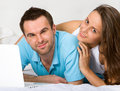 Couple with laptop in bedroom Stock Images