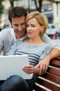 Couple on laptop on bench Royalty Free Stock Photography