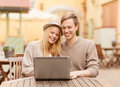 Couple with laptop in cafe summer holidays city dating and technology concept Stock Photography