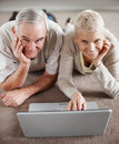 Couple with a laptop computer lying on the floor Royalty Free Stock Photos