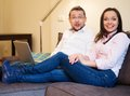 Couple with laptop in home interior surprised young on a sofa Royalty Free Stock Photos