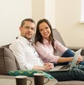 Couple with laptop in home interior young cheerful on a sofa Royalty Free Stock Photos