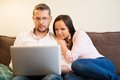 Couple with laptop in home interior young cheerful on a sofa Royalty Free Stock Photo