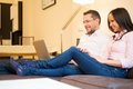 Couple with laptop in home interior young cheerful on a sofa Royalty Free Stock Photography