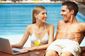 Couple with laptop at pool Royalty Free Stock Photo