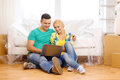 Couple with laptop sitting on floor in new house moving home technology and concept smiling Royalty Free Stock Images