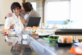 Couple with laptop in sushi bar, man kissing woman Royalty Free Stock Photo