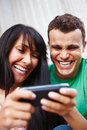 Couple laughing at modern mobile phone Stock Images