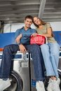 Couple with laundry basket sitting on washing low angle view of loving young machines Stock Photo