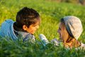 Couple laying in grass field at sunset. Stock Images