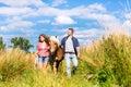 Couple leading horse thru meadow summer Royalty Free Stock Photos