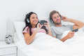 Couple listening to music in their bed beautiful Stock Images