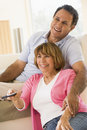 Couple in living room with remote control smiling Royalty Free Stock Image
