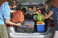 Couple loading luggage into car trunk two young sons watching parents load in Stock Photography