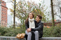 Couple looking away while sitting on parapet young women man s lap Royalty Free Stock Images