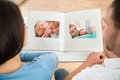 Couple looking at baby's photo album Royalty Free Stock Photo