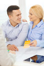 Couple looking at blueprint and color samples home designe architecture concept smiling office Stock Photo