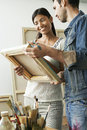 Couple looking at canvases in artist studio happy multiethnic Royalty Free Stock Image