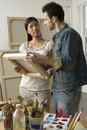 Couple looking at canvases in artist studio multiethnic Royalty Free Stock Images