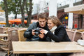 Couple looking at digital camera young photographs on outdoor restaurant Royalty Free Stock Image