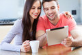 Couple looking at digital tablet smiling with Royalty Free Stock Images