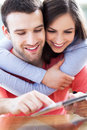Couple looking at digital tablet smiling with Stock Photography