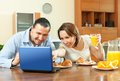 Couple looking e mai during breakfast happy ordinary using laptop at home Stock Photo