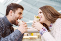 Couple looking at each other while eating fast food Royalty Free Stock Photo