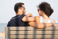 Couple looking each other in the eyes sitting on bench during sunset with shadows Stock Photography