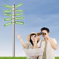 Couple looking for holiday option using binoculars with road signs beside them Stock Photo