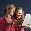 Couple looking at a laptop computer adult and teenager mother and daughter the screen and smiling Stock Photo