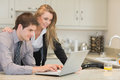 Couple looking at the laptop in kitchen Stock Image
