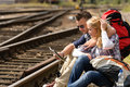 Couple looking at map sitting on railroad Stock Images