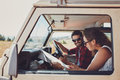 Couple looking at the map in their car man and women on a road trip and reading a together while seated inside happy young going Royalty Free Stock Photography
