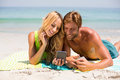 Couple looking in mobile phone while lying at beach Royalty Free Stock Photo