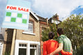 Couple looking at new home with for sale sign rear view of young Stock Images