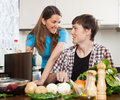 Couple looking at notebook during cooking food Royalty Free Stock Photo