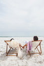 Couple looking ocean on their deck chairs beach Royalty Free Stock Photos