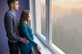 The couple is looking out the window which waiting for a child Stock Photography